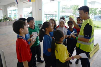 Children learning about road signs from a volunteer