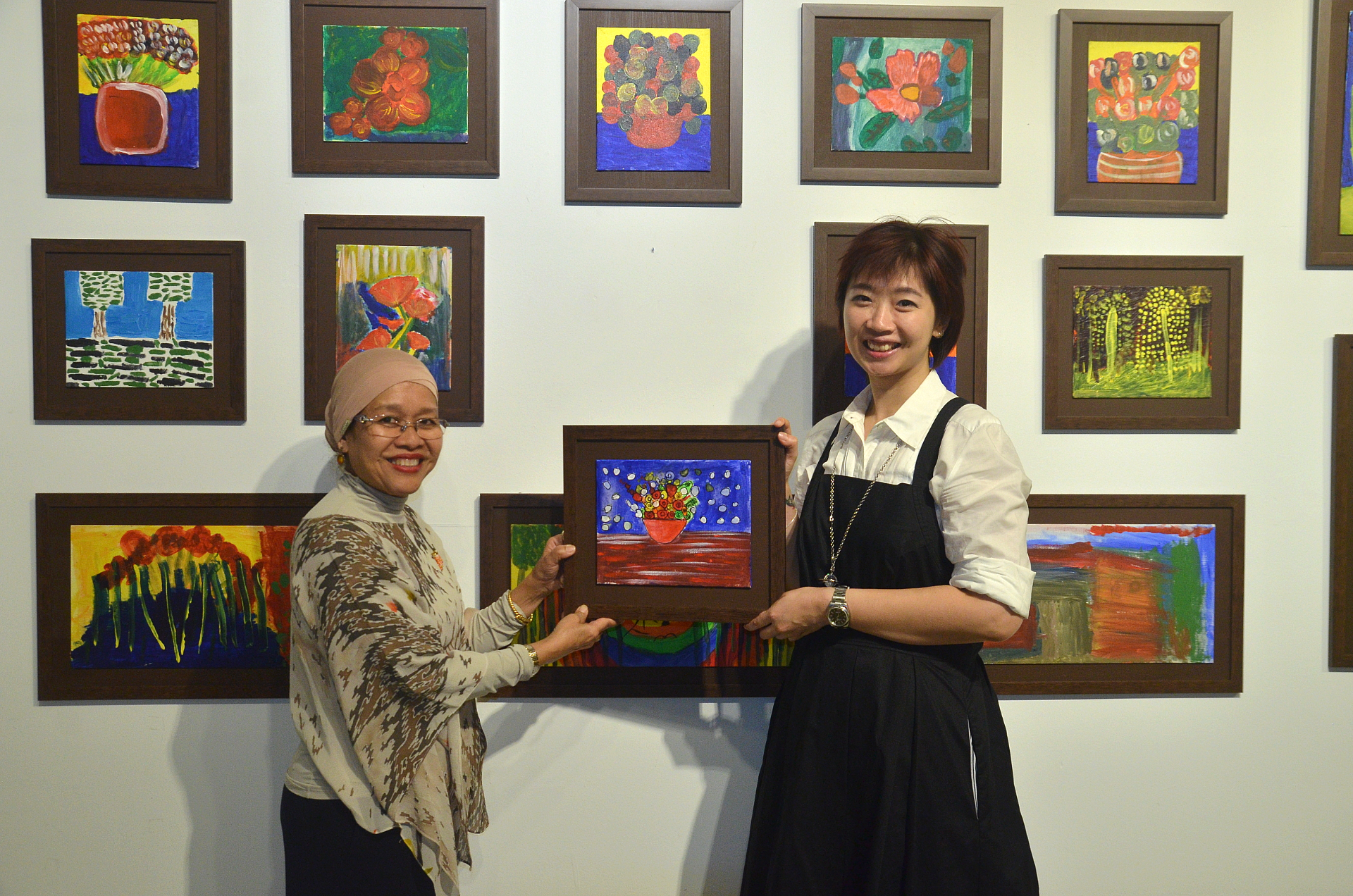 Juairiah Johari, Founder of GOLD and Dr Tong Gin Chee, Co-Founder of ZHAN Art Space hanging up the final artpiece
